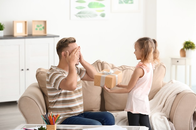 Śliczna mała dziewczynka wita swojego tatę dniem ojca w domu