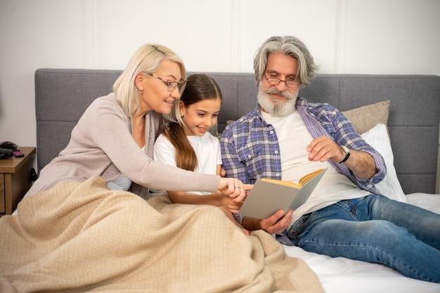 Śliczna mała dziewczynka wnuczka czytająca książkę ze swoimi pozytywnymi dziadkami leżąc na łóżku
