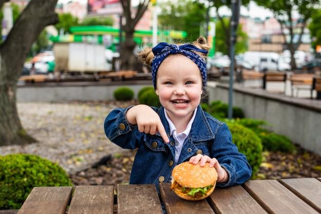 Śliczna mała dziewczynka wskazała na burgera przed jedzeniem w kawiarni na świeżym powietrzu