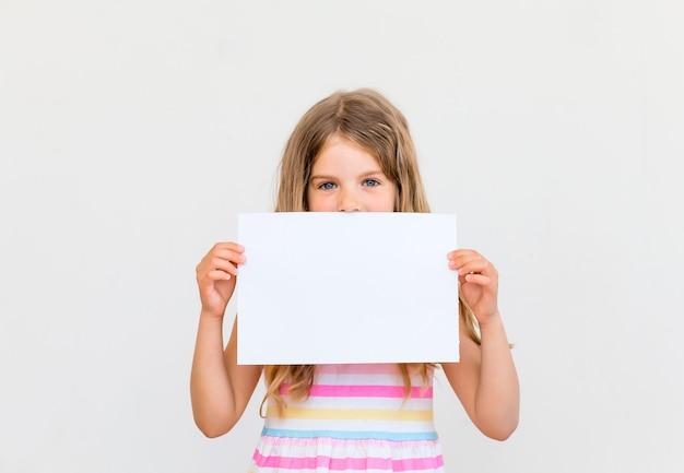 Śliczna mała dziewczynka z białym czystym papierem. oddziel na białym tle. wolna przestrzeń