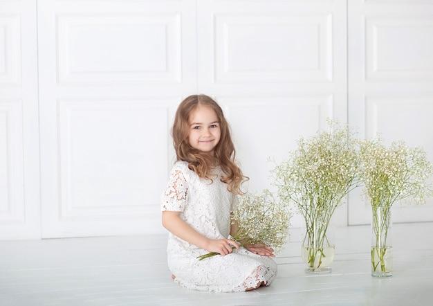 Śliczna mała dziewczynka z bukietem łyszczec (baby-breathon). portret dziewczyny z blond włosami w białej sukni z kwiatami. słodkie dziecko z bukietem w ręce. 8 marca dzień matki