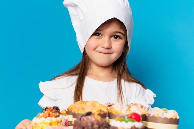 Śliczna mała dziewczynka z ciastami