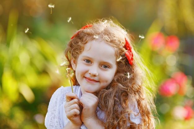 Śliczna mała dziewczynka z dandelion kwiatem w wiosna parku