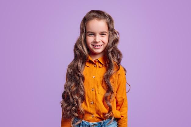 Śliczna mała dziewczynka z długimi falującymi brązowymi włosami w jasnej pomarańczowej koszuli, patrząc z czarującym uśmiechem