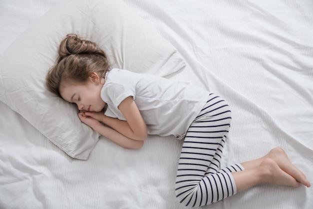 Śliczna mała dziewczynka z długimi włosami śpi w łóżku.