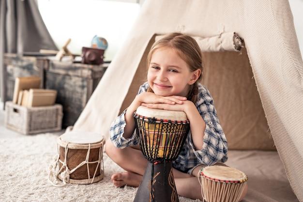Śliczna mała dziewczynka z etnicznymi bębnami siedzi w pobliżu wigwamu w pokoju zabaw