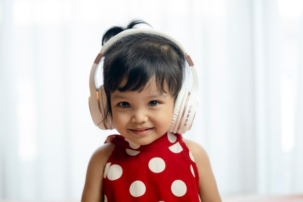 Śliczna mała dziewczynka z hełmofonami w domu