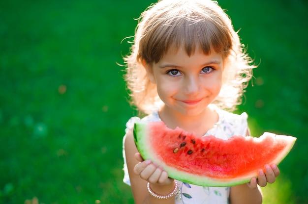 Śliczna mała dziewczynka z heterochromią dwa kolorowe oczy jedzą arbuza i cieszą się piknikiem w parku. natura, styl życia