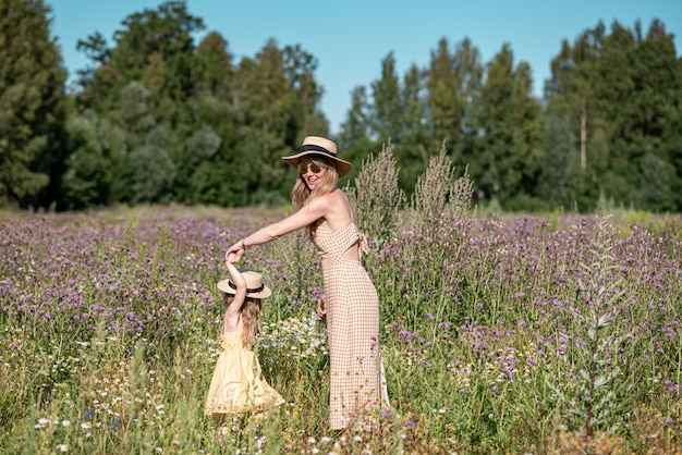 Śliczna mała dziewczynka z jej matką chodzi w kwiatu polu