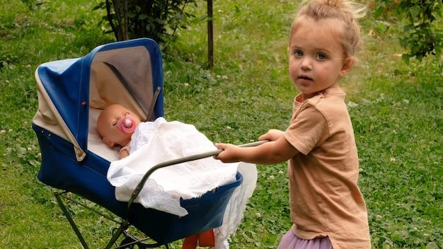 Śliczna mała dziewczynka z jej wózkiem zabawek