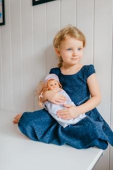 Śliczna mała dziewczynka z krótkimi jasnymi włosami w niebieskiej sukience trzyma swoją uroczą zabawkę barbie, siedzi w jasnym pokoju dziecka i uśmiecha się