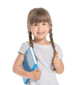 Śliczna mała dziewczynka z książką pokazuje kciuk na białym tle