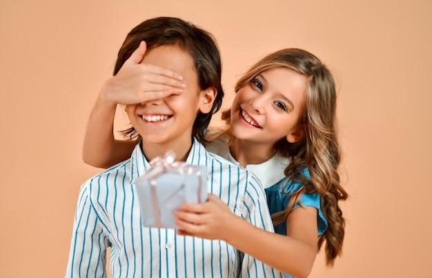 Śliczna mała dziewczynka z lokami w niebieskiej sukience zamyka oczy miłego przystojnego chłopca w koszuli i daje mu prezent na białym tle