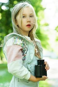 Śliczna mała dziewczynka z lornetką retro w miejskim parku