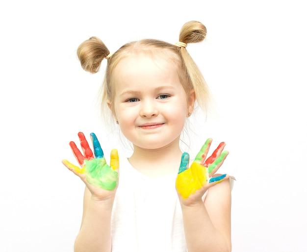 Śliczna mała dziewczynka z malowanymi rękami. na białym tle