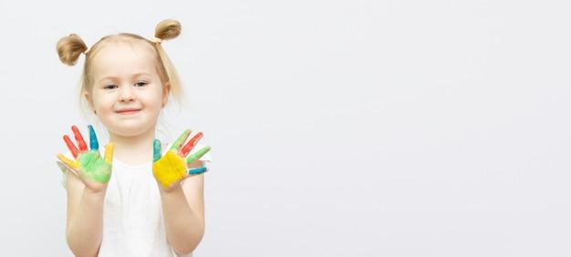 Śliczna mała dziewczynka z malowanymi rękami. samodzielnie na białym tle. miejsce na kopię banera