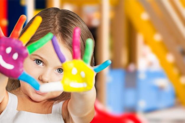 Śliczna mała dziewczynka z malowanymi rękami
