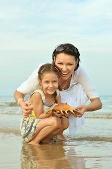 Śliczna mała dziewczynka z matką na plaży z muszlą