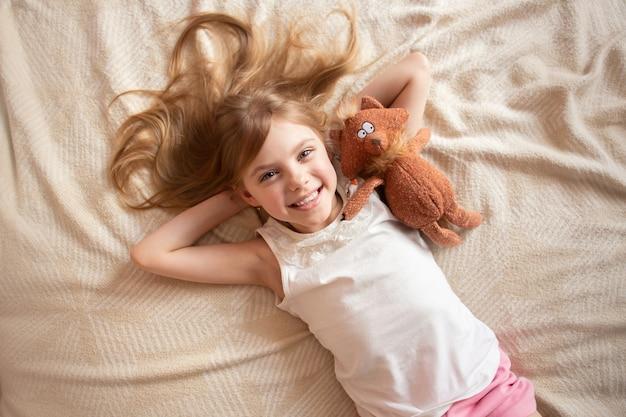 Śliczna mała dziewczynka z miękką zabawką na leżance