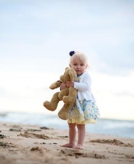 Śliczna mała dziewczynka z misiem na plaży