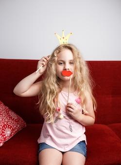 Śliczna mała dziewczynka z papierową koroną i czerwonymi ustami siedzi na czerwonym krześle w domu.