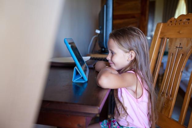 Śliczna mała dziewczynka z pastylka komputerem indoors