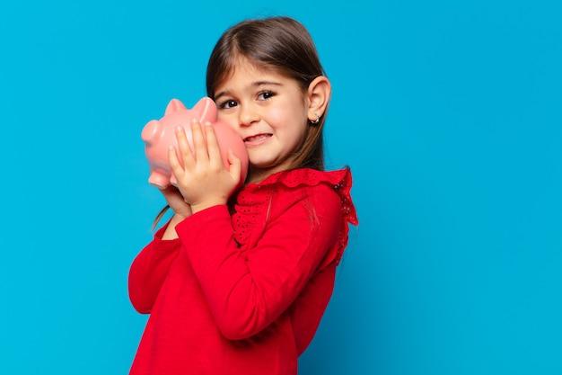 Śliczna mała dziewczynka z przerażonym wyrazem twarzy i trzymająca skarbonkę