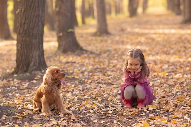 Śliczna mała dziewczynka z psem w jesienny park z pomarańczowymi i żółtymi liśćmi.