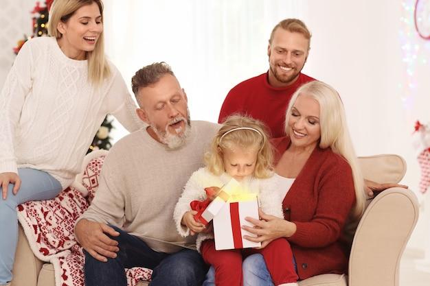 Śliczna mała dziewczynka z rodziną otwiera świąteczne pudełko w domu
