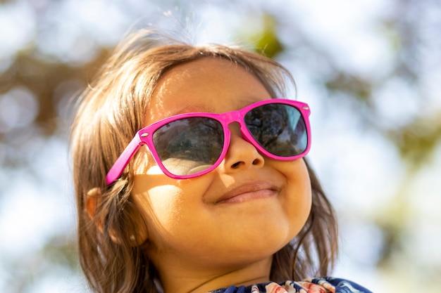 Śliczna mała dziewczynka z różowymi okularami przeciwsłonecznymi