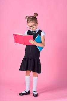 Śliczna mała dziewczynka z szkłami i książkami na menchii przestrzeni, przestrzeń dla teksta. koncepcja czytania