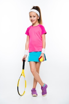 Śliczna mała dziewczynka z tenisowym kantem i piłką w ona ręki