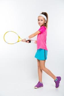 Śliczna mała dziewczynka z tenisowym kantem w jej rękach na białym tle