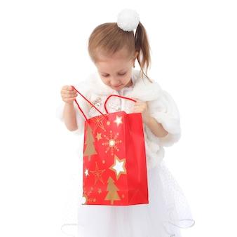 Śliczna mała dziewczynka z torbą na prezent świąteczny