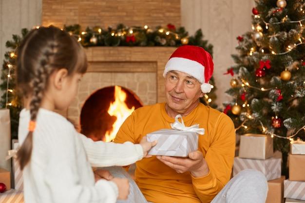 Śliczna mała dziewczynka z warkoczykami daje prezenty na boże narodzenie swojemu ulubionemu dziadkowi, staruszek patrzy na dziecko z miłością, ubrany w czapkę mikołaja i żółty sweter, pozuje w świątecznym salonie.
