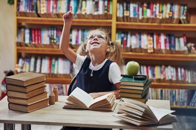 Śliczna mała dziewczynka z warkoczykami jest w bibliotece