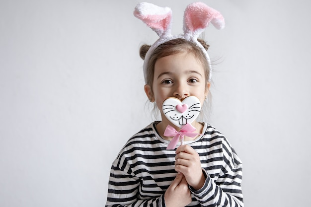 Śliczna mała dziewczynka z wielkanocnymi piernikami na patyku i ozdobnymi uszami króliczka na głowie.
