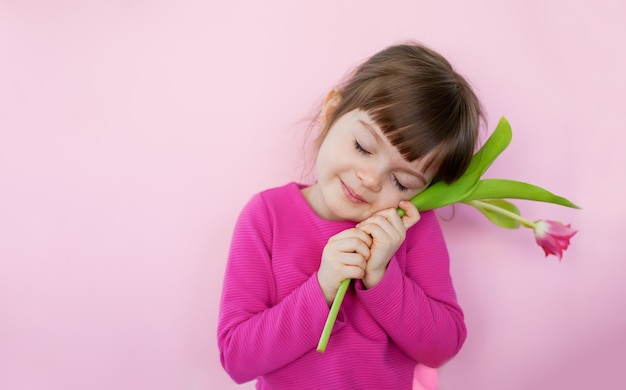 Śliczna mała dziewczynka z zamkniętymi oczami w różowej sukience trzymająca różowego tulipana