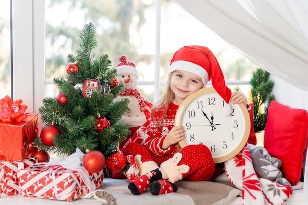 Śliczna mała dziewczynka z zegarkiem w dłoniach siedzi na parapecie w oknie domu przy choince i czeka na nowy rok lub boże narodzenie w czapce świętego mikołaja i uśmiecha się