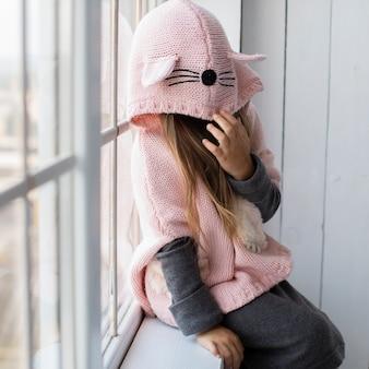 Śliczna mała dziewczynka zakrywa jej twarz