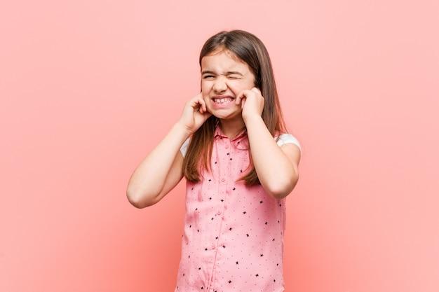 Śliczna mała dziewczynka zakrywa ucho z jego rękami.