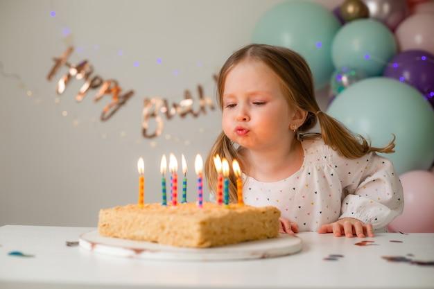 Śliczna mała dziewczynka zdmuchuje świeczki na urodzinowym torcie w domu na tle balonów. urodziny dziecka