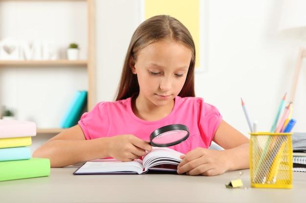 Śliczna mała dziewczynka ze słabym wzrokiem czyta przez lupę