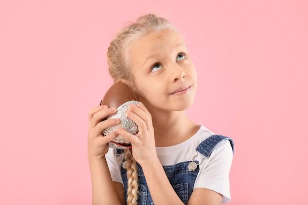Śliczna mała dziewczynka ze słodkim czekoladowym jajkiem na kolorowym tle
