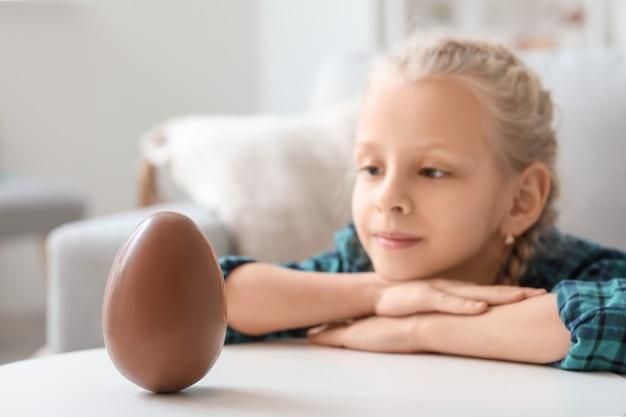 Śliczna mała dziewczynka ze słodkim czekoladowym jajkiem w domu