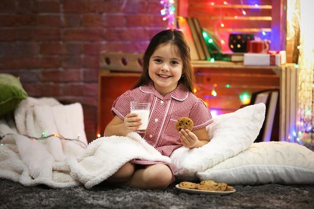 Śliczna mała dziewczynka ze szklanką mleka i smacznymi ciasteczkami w świątecznym pokoju