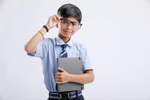 Śliczna mała indiańska / azjatycka szkolna chłopiec z nutową książką odizolowywająca