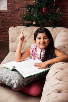 Śliczna mała indyjska azjatycka dziewczyna czytająca książkę siedząc na kanapie lub kanapie w domu
