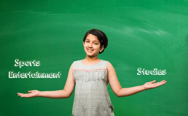 Śliczna mała indyjska azjatycka uczennica z różnymi wyrażeniami, stojąca na tle zielonej tablicy pełnej edukacyjnych gryzmołów