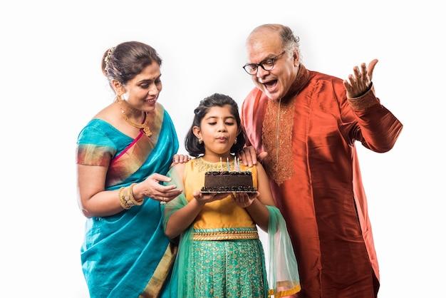 Śliczna mała indyjska azjatycka wnuczka lub dziewczyna świętująca urodziny z dziadkami podczas noszenia etnicznych ubrań